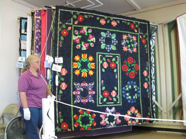 Flower garlands are the theme in this quilt, but each medallion uses a different pattern, and the center differs from any of the surrounding blocks.