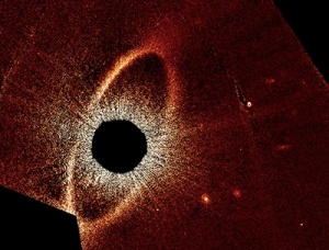 A planetary system forming. (The black center is a mask over the star.) Photo Source